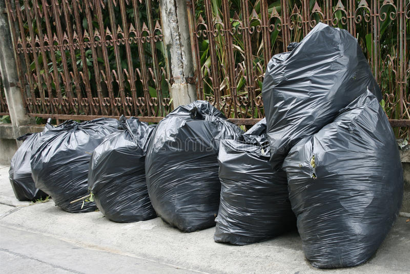 Black garbage bags. On the ground to await disposal royalty free stock image