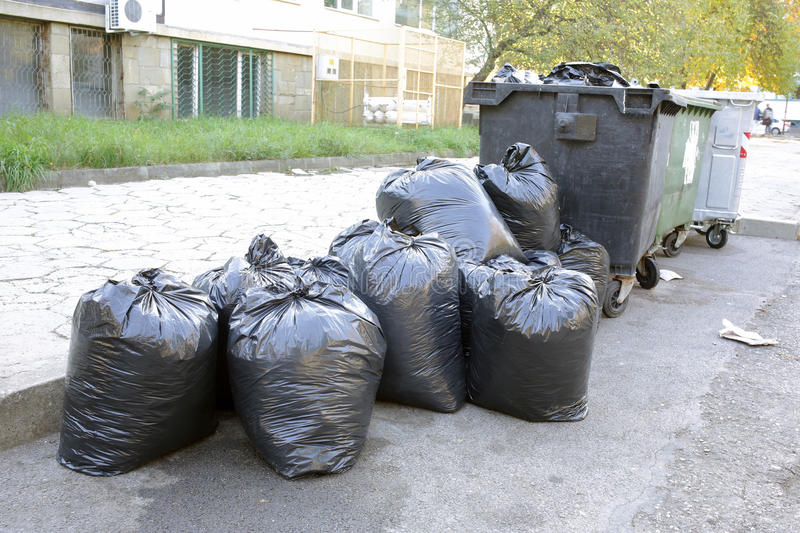 Black garbage bags. On the street near trash recycle bins stock photography