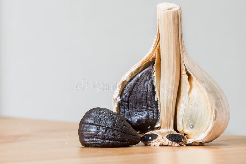 Black garlic close up shot with cloves and whole garlic. royalty free stock photos