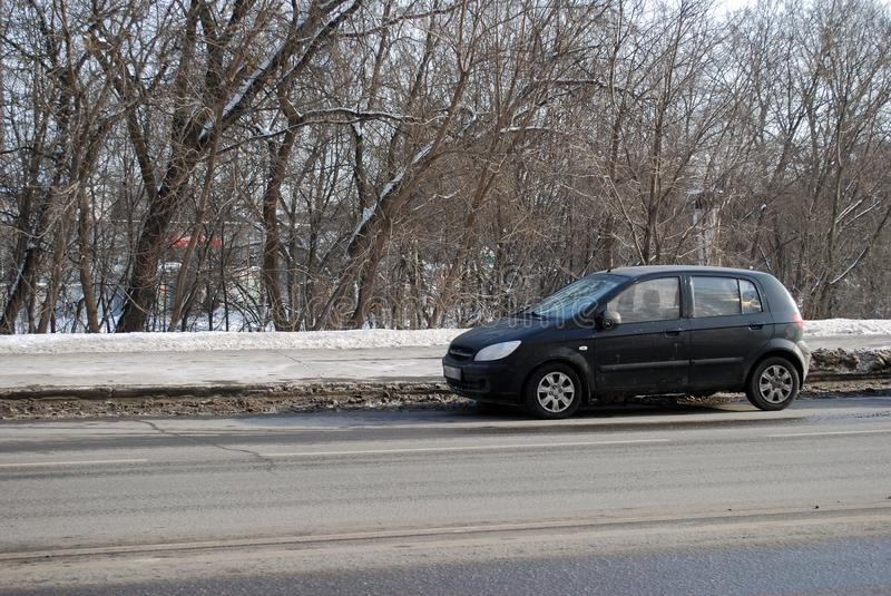 The black Getz Hyundai car costs parked on the road in the winter afternoon. City landscape stock photos