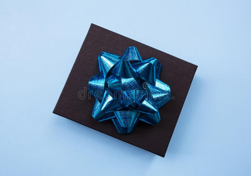 Black gift box on a blue contrasted background, decorated with a blue bow, creating a romantic atmosphere. Typically used for birt. Hday, anniversary presents stock photos