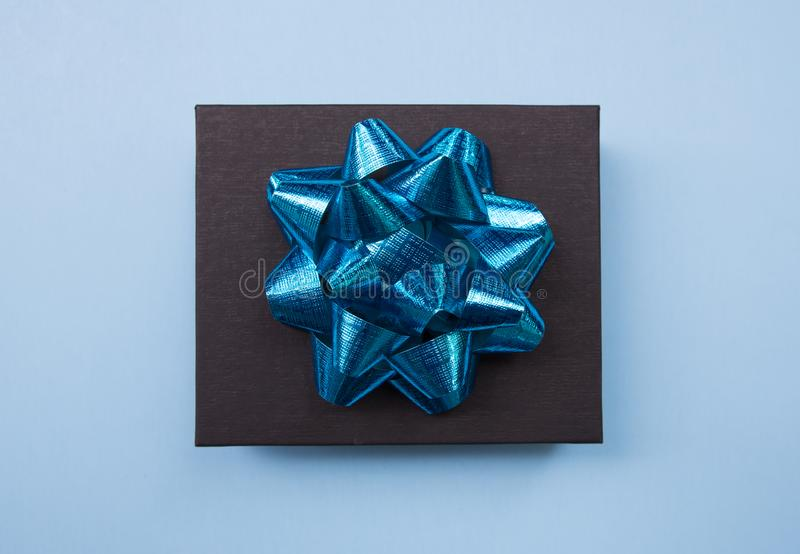 Black gift box on a blue contrasted background, decorated with a blue bow, creating a romantic atmosphere. Typically used for birt. Hday, anniversary presents royalty free stock photos