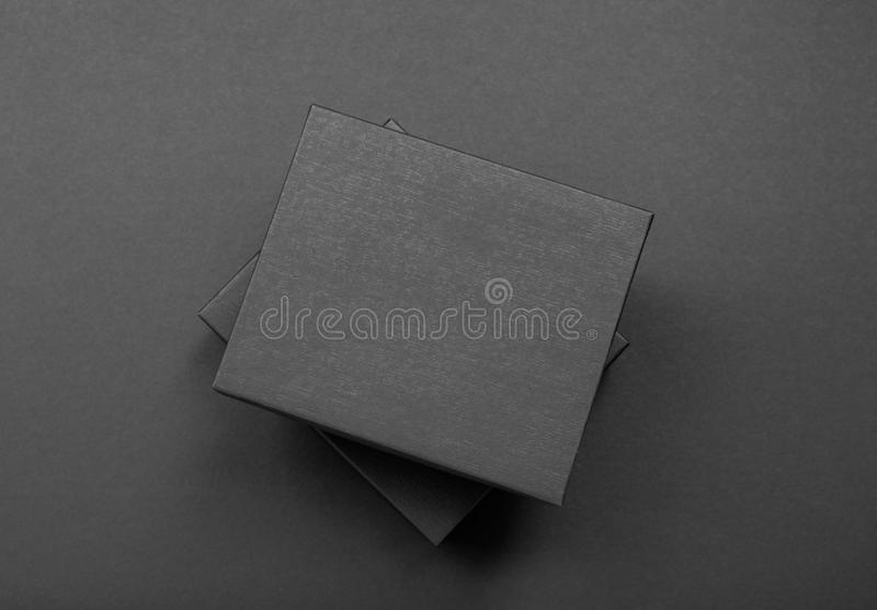 Black gift box on a dark contrasted background, creating a romantic atmosphere. Typically used for birthday, a. Nniversary presents, gift cards, post cards royalty free stock photo