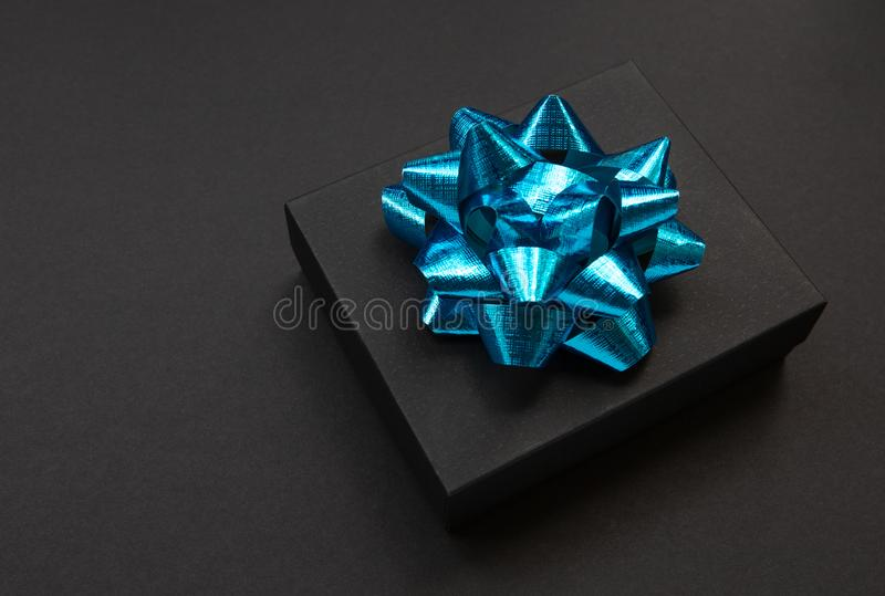 Black gift box on a dark contrasted background,decorated with a blue color bow, creating a romantic atmosphere. Typically used for. Black gift box on a dark stock photography
