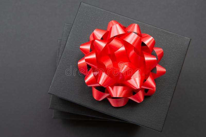 Black gift box on a dark contrasted background, decorated with a red color bow, creating a romantic atmosphere. Typically used for. Birthday, anniversary royalty free stock image