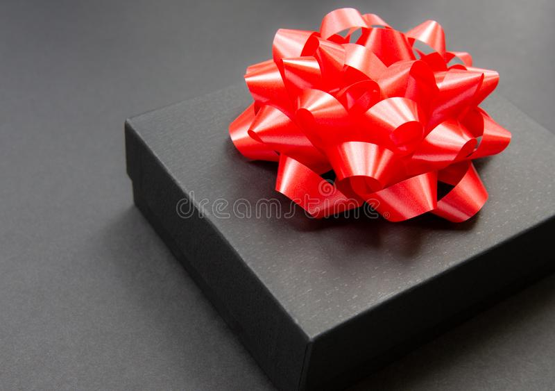 Black gift box on a dark contrasted background, decorated with a red color bow, creating a romantic atmosphere. Typically used for. Birthday, anniversary stock image