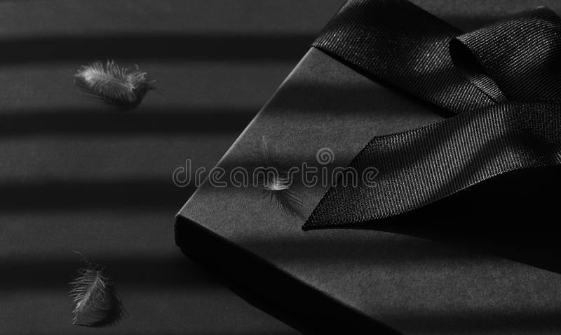 Black gift box on a dark contrasted background. Black gift box on a dark contrasted background, decorated with a textured bow and feathers, creating a romantic royalty free stock photography