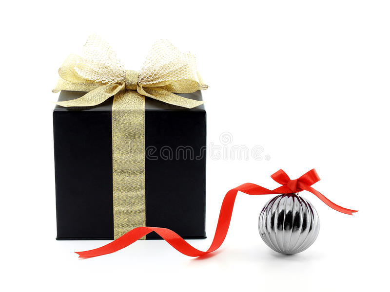 black cube shape cardboard gift box with golden ribbon net bow and metallic glossy gray christmas ball with red bow stock photo