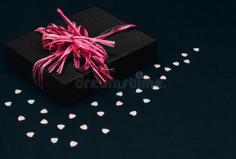 Black gift box with pink ribbon bow on black background sprinkled with heart shaped confetti. Copy space. royalty free stock image