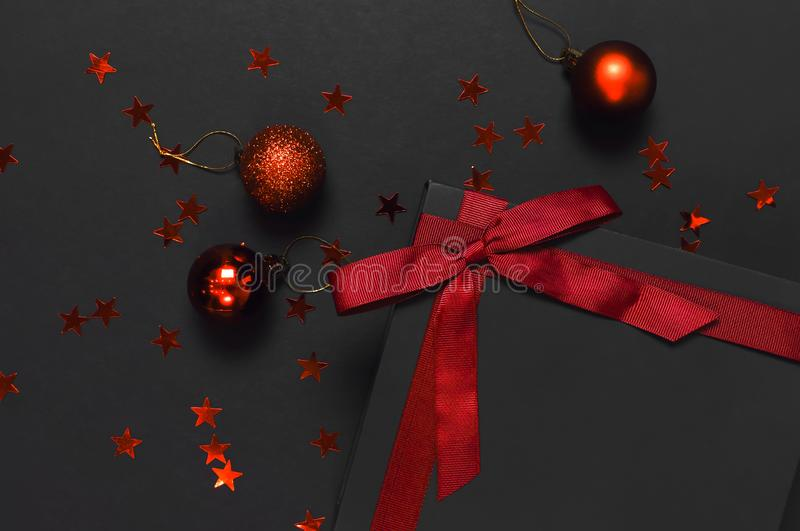 Black gift box with red ribbon, Christmas balls, red holographic glitter confetti on dark background top view flat lay. Holiday stock photo