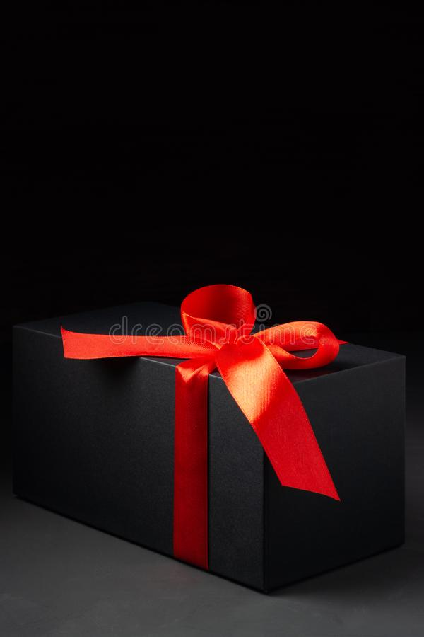 Black gift box with red ribbon on dark background royalty free stock photography