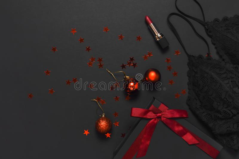 Black gift box with red ribbon, lace bra underwear, red lipstick, Christmas balls, holographic confetti on dark background top royalty free stock photos