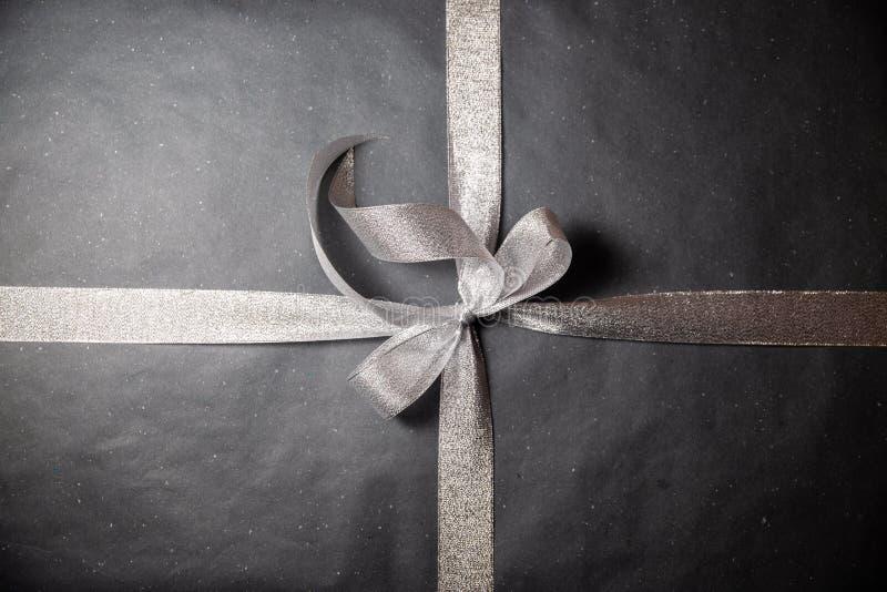 Black gift box with silver ribbon stock image
