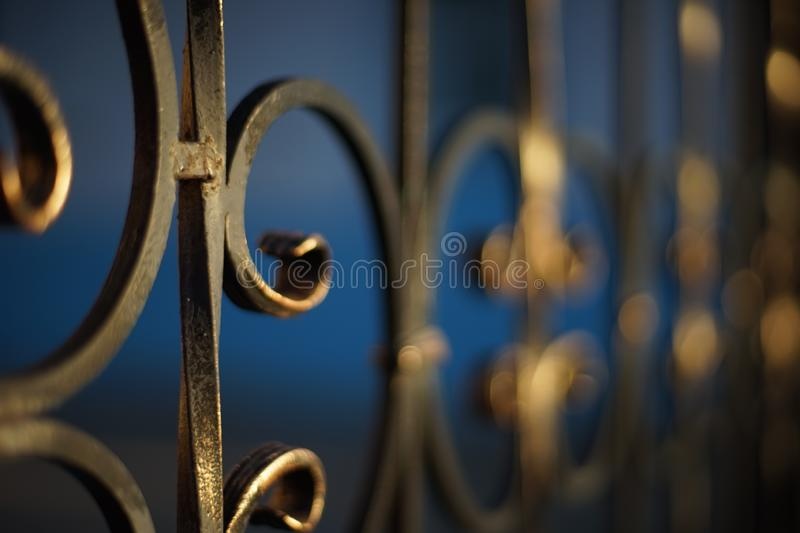 Black with gilded patina forged fence with curls royalty free stock images