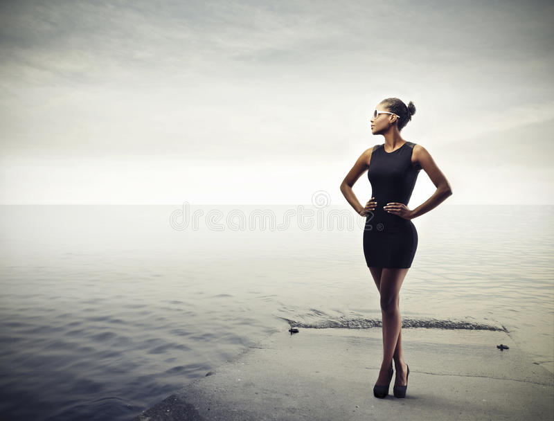 Black Girl. In black standing on a pier royalty free stock photos