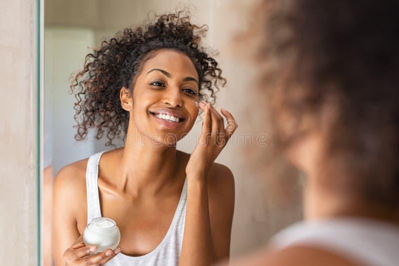 Black girl applying lotion on face stock photo