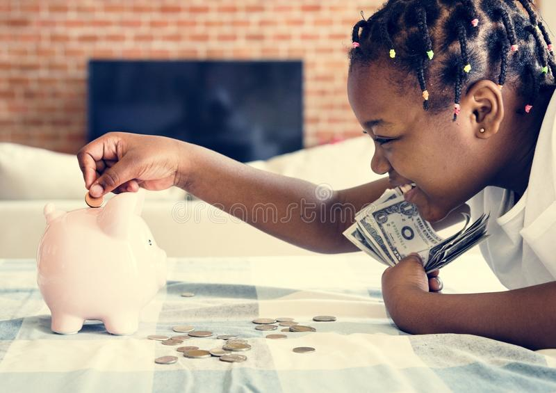 Black girl collecting money to piggy bank royalty free stock image