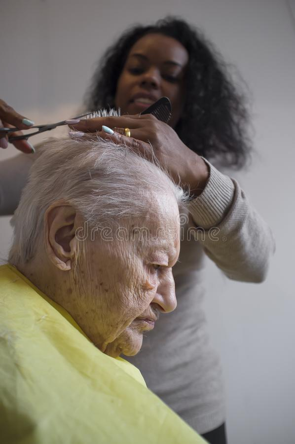 Black girl cuts hair to old white woman. Black caregiver girl cuts hair to elderly caucasian woman stock photos