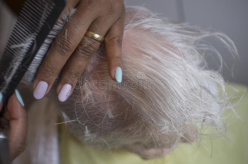 Black girl cuts hair to old white woman. Black caregiver girl cuts hair to elderly caucasian woman stock images