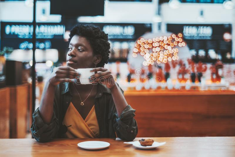 Black girl drinking coffee indoors stock photography