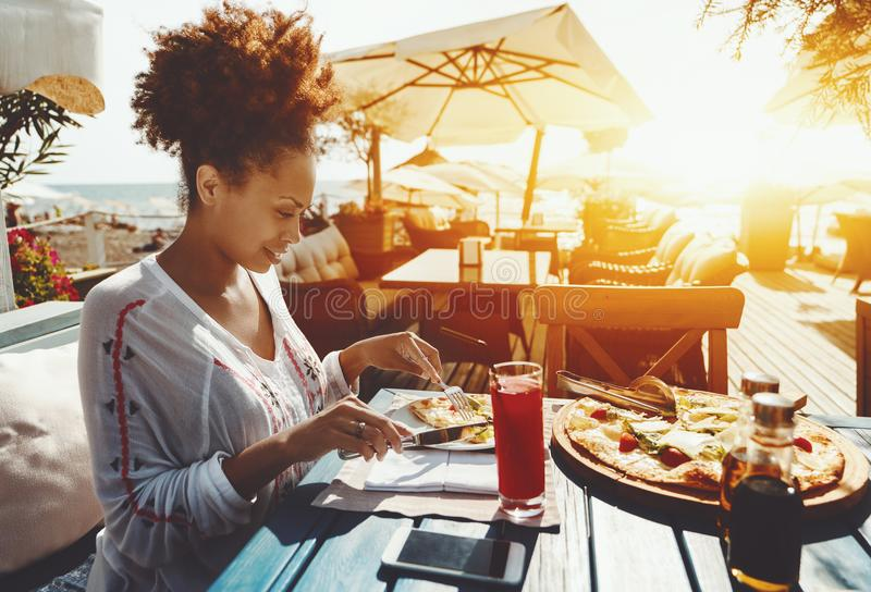 Black girl eating pizza in street cafe royalty free stock images