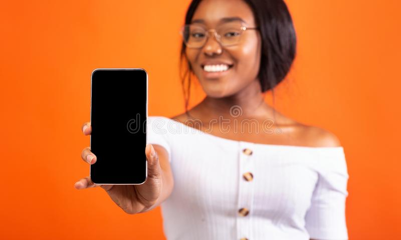 Black Girl Showing Phone Empty Screen Standing, Orange Background, Mockup royalty free stock images