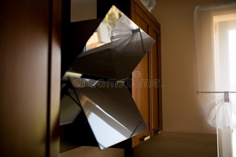 Ventilation hood made of glass in the kitchen, with reflection. View from side. Wooden furniture in the background royalty free stock images