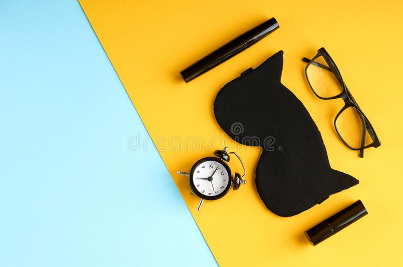 Black glasses, alarm clock, mascara, pomade and sleep mask on blue and yellow background composition. Flat lay and top view photo, time, make-up, cosmetics stock images