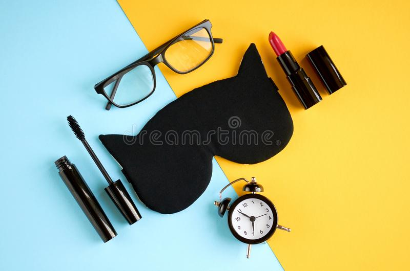 Black glasses, alarm clock, mascara, pomade and sleep mask on blue and yellow background composition. Flat lay and top view photo, time, make-up, cosmetics stock photography