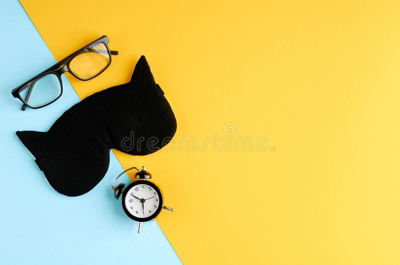Black glasses, alarm clock and sleep mask on blue and yellow background composition. Flat lay and top view photo, time, watches, spectacles, eyeglasses royalty free stock photo
