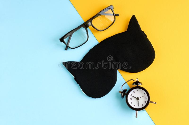 Black glasses, alarm clock and sleep mask on blue and yellow background composition. Flat lay and top view photo, time, watches, spectacles, eyeglasses royalty free stock photography