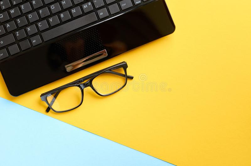 Black glasses and laptop keyboard on blue and yellow background composition. Flat lay and top view photo, computer, pc, spectacles, eyeglasses, eyewear, golden royalty free stock photography