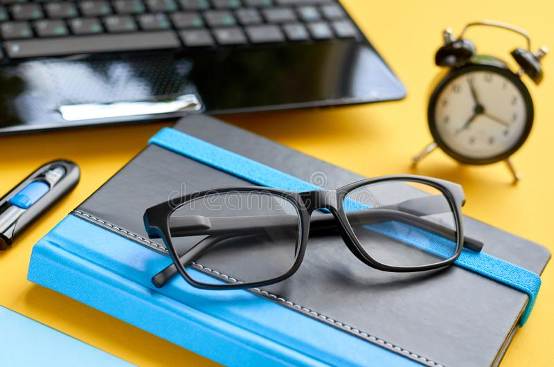 Black glasses, notebook, usb flash and laptop keyboard on blue and yellow background composition. Flat lay and top view photo, alarm, drive, notepad, clock stock photo