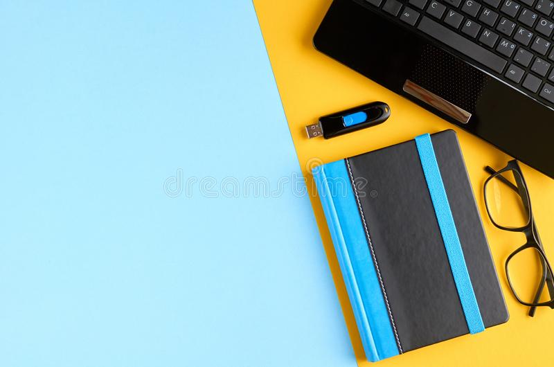 Black glasses, notebook, usb flash and laptop keyboard on blue and yellow background composition. Flat lay and top view photo, drive, notepad, computer, pc stock photography