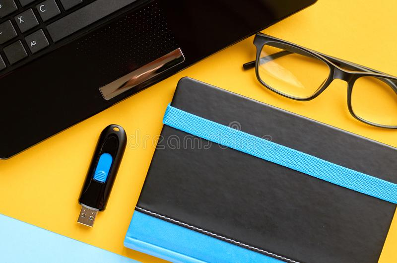 Black glasses, notebook, usb flash and laptop keyboard on blue and yellow background composition. Flat lay and top view photo, drive, notepad, computer, pc stock photos