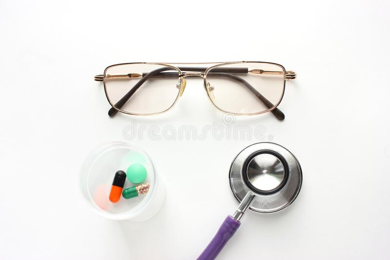 Black glasses and tablets stethoscope on a light table, close-ups. Stethoscope on a light table stock photos