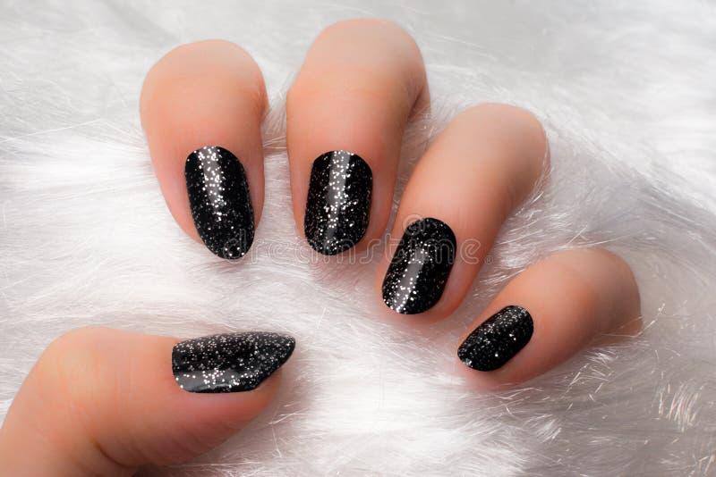 Black glittered nails stock photos