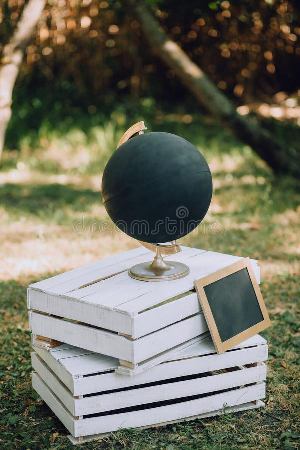 A black globe with a slate stands on wooden pallets on the grass. Wedding Original Decor. Vertical stock photo