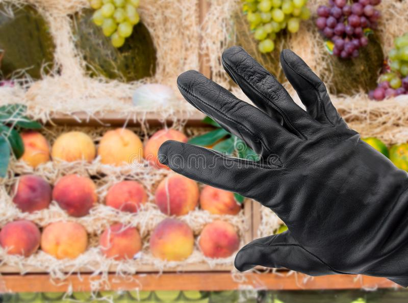 Stealing from the greengrocer. Black gloved hand of a thief stealing fruit from a store royalty free stock photos