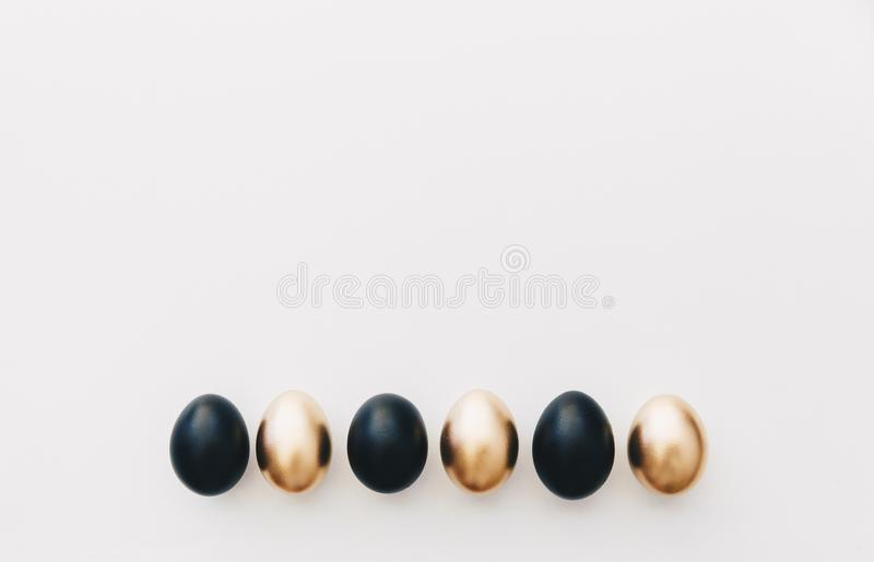 Black and gold eggs. Minimal easter background royalty free stock image