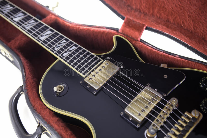 Black and gold electric guitar in red fur-lined case. Classic black and gold vintage electric guitar in red fur-lined case royalty free stock images