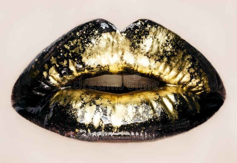 Black and gold lips close up. Macro photography royalty free stock photos
