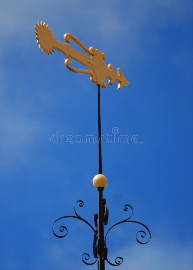 Black and gold stylized fish weather vane against deep blue sky. royalty free stock photography