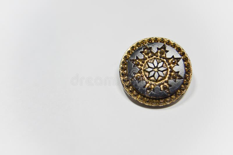 Black and golden ornamented button with floral mandala pattern on the front side. Selective focus. Handcraft concept stock photography