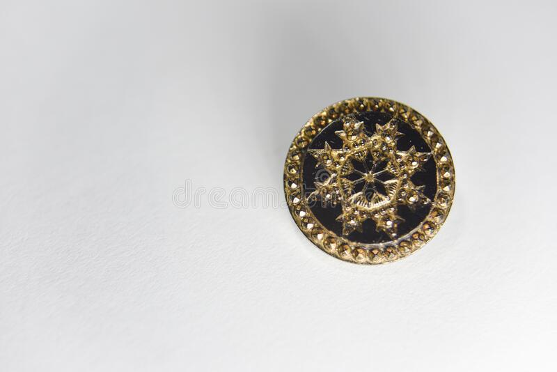 Black and golden ornamented button with floral mandala pattern on the front side. Selective focus. Side light from the bottom line, handcraft concept stock photos