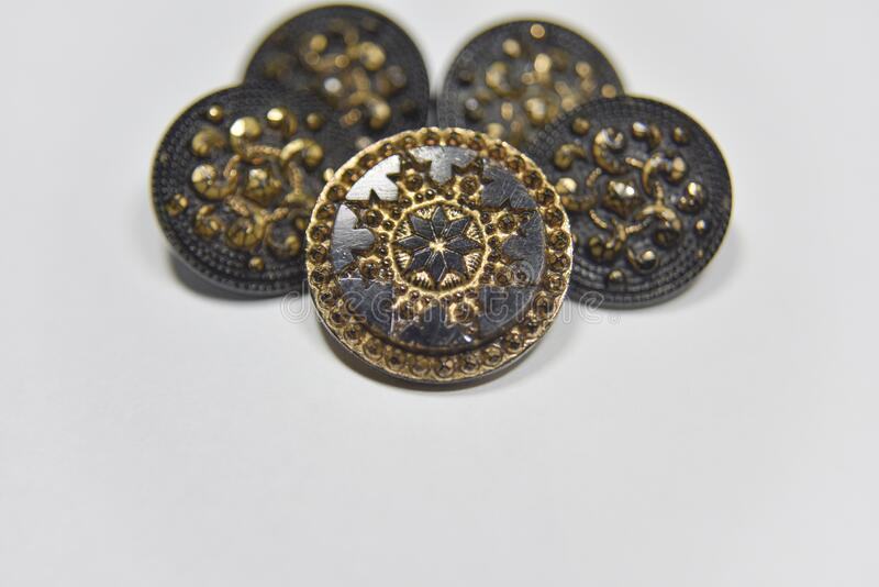 Black and golden ornamented buttons with floral mandala pattern on the front side. Selective focus. Handcraft concept stock images