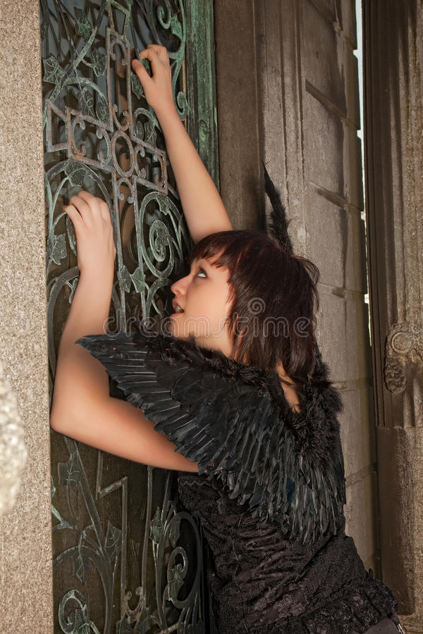 Black gothic angel. Gothic woman with black wings knocking on an antique door in a cemetery stock image