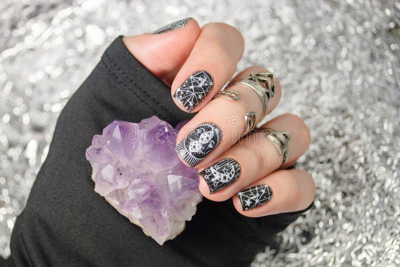 Black gothic manicure with mystic nail art. Amethyst in the hand on the silver sparkle background royalty free stock photos