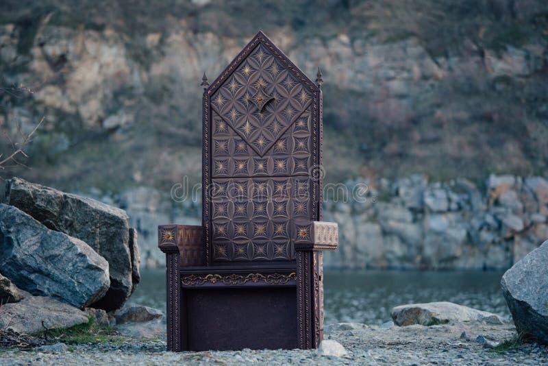 Black gothic throne. Against the dark rocky mountains, vampire, hip toning, creative color, dark-Boho royalty free stock photos