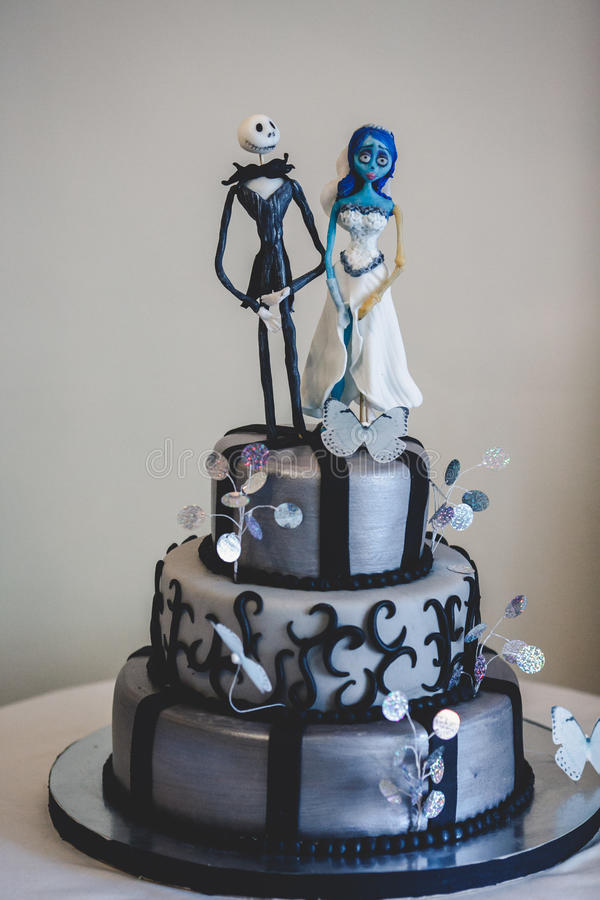 Black gothic wedding cake decorated with figures of cartoon's he. Roes a stock photos